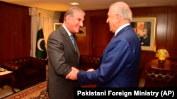 Pakistani Foreign Minister Shah Mahmood Qureshi (left) receives U.S. envoy Zalmay Khalilzad at the Foreign Ministry in Islamabad on January 18.