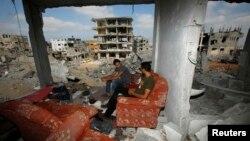 Палестинці в місті Газа у своєму будинку, зруйнованому, за їхніми словами, внаслідок повітряного удару Ізраїлю, фото 27 серпня 2014 року