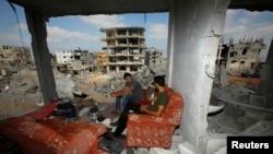 Палестинцы на руинах разрушенного дома в Газе, 27 августа 2014 года.