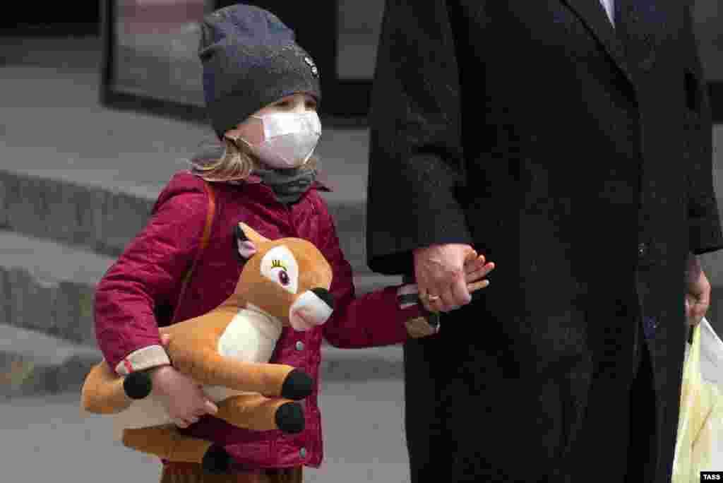 Дитина в простій медичній масці. Ефективний захист така маска забезпечує протягом двох годин, потім її змінюють
