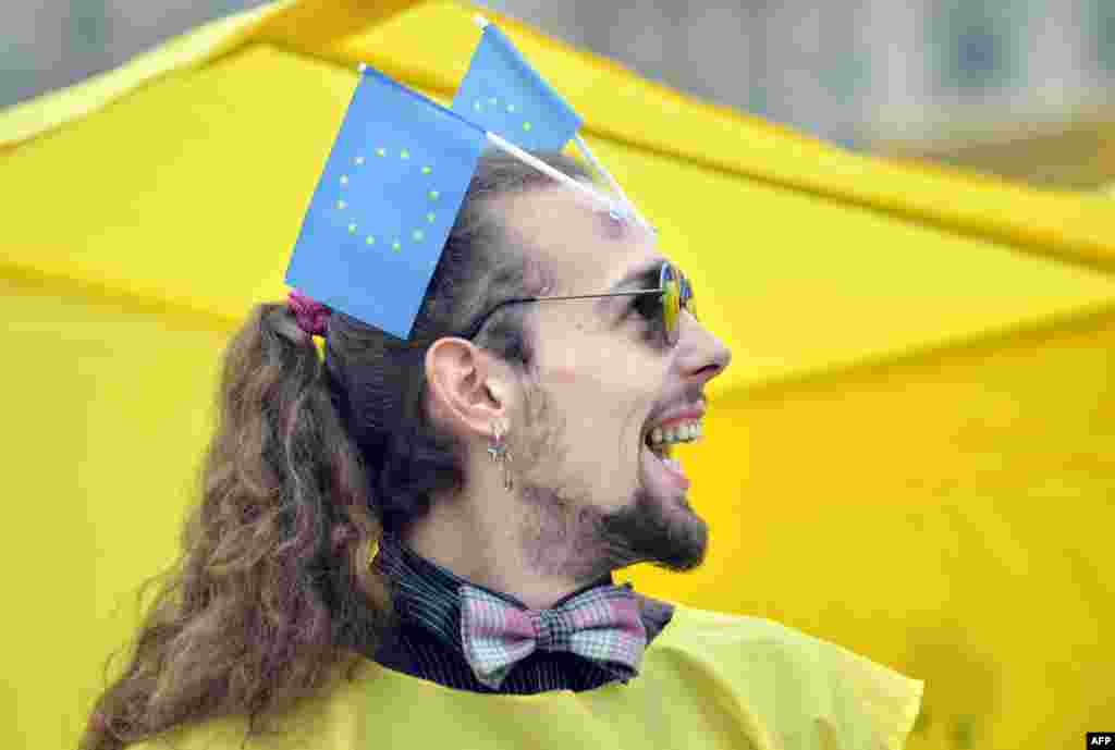 "An activist of the Ukrainian movement ""For A European Future"" smiles as he places EU flags on his forehead during a rally on Independence Square in Kyiv on October 30. (AFP/Sergei Supinsky)"