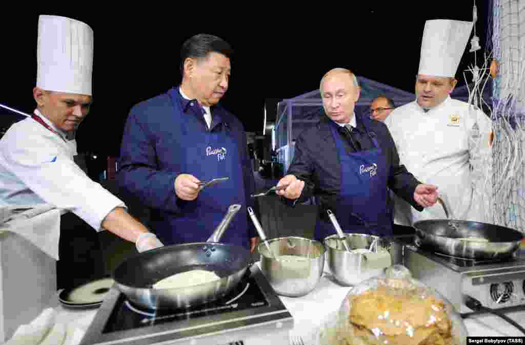 China's President Xi Jinping (second from left) and Russia's President Vladimir Putin (second from right) make bliny, or Russian pancakes, as they visit the Far East Street exhibition on the sidelines of the 2018 Eastern Economic Forum on Russky Island, near Vladivostok. (TASS/Sergei Bobylev)