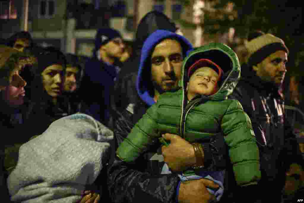 A man carrying his child waits with other migrants and refugees to be registered in a refugee center in Presevo, Serbia, after crossing the Macedonia-Serbia border. (AFP/Armend Nimani)