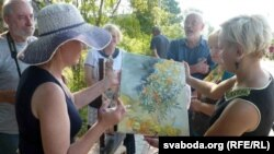 Сьвятлана Баранкоўская (зьлева) дорыць сваю карціну прадстаўніцам райвыканкаму