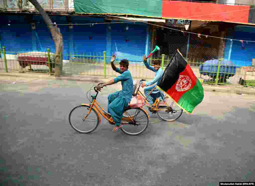 A boy waves Afghanistan's national flag as he rides his bicycle on Independence Day in Jalalabad on August 18. (epa-EFE/Ghulamullah Habibi)