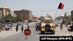 Afghan security officials and private militia members patrol in Herat on August 4.