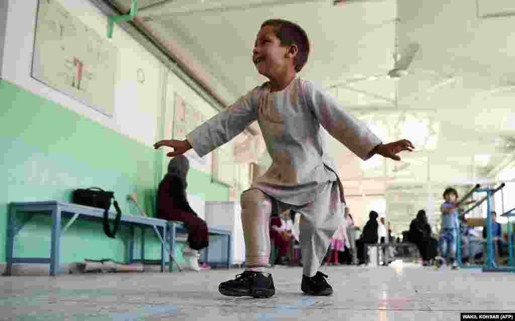 Ahmad Sayed Rahman, a five-year-old Afghan boy who lost his right leg when he was hit by a bullet in the cross fire of a battle, dances with his prosthetic leg at the International Committee of the Red Cross hospital for war victims and the disabled, in Kabul on May 7. (AFP/Wakil Kohsar)