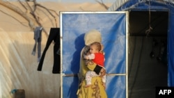 An Iraqi woman carries a child at the Al-Khazir camp for internally displaced people.
