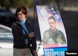 Донецк - женщина с плакатом, агитирующим голосовать за Александра Захарченко