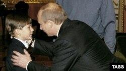 Президент России Владимир Путин приветствует шестилетнего мальчика Андрея Сенько во время его визита в Киев. 27 октября 2004 года