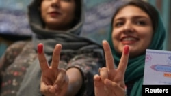 Iranian women show their ink-stained fingers after casting their votes during the presidential election in Tehran on May 19.
