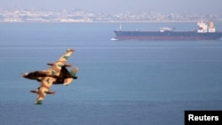 Iran -- An Iranian military fighter plane flies past an oil tanker during naval manoeuvres in the Persian Gulf and Sea of Oman, April 5, 2006