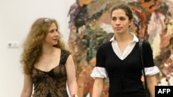 Maria Alyokhina (left) and Nadezhda Tolokonnikova, who were jailed for nearly two years over a Pussy Riot protest action, arrive at a preview of nominees for the inaugural Prudential Eye Awards in Singapore on January 17.