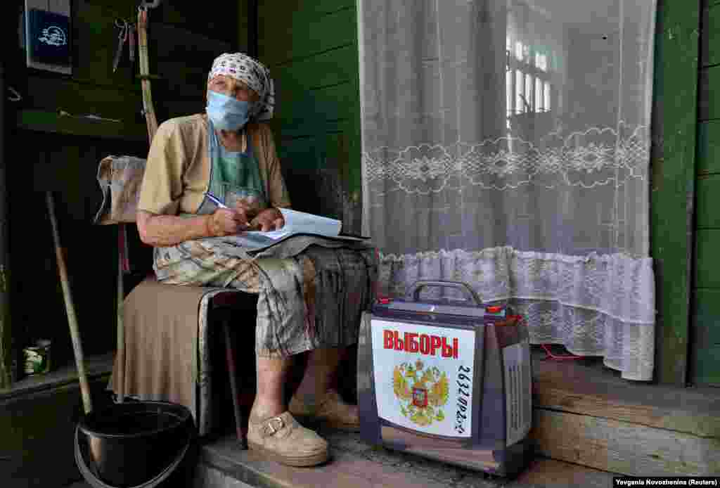 A local resident fills in documents near a mobile ballot box outside her house during a seven-day vote on constitutional reforms in the village of Troitskoye in the Moscow region on June 25. (Reuters/Evgenia Novozhenina)