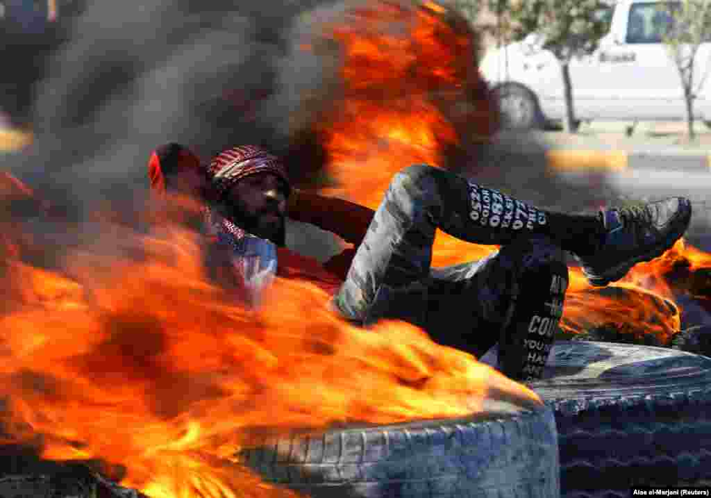 An Iraqi demonstrator sits amid burning tires blocking a road during ongoing anti-government protests in Najaf, Iraq. (Reuters/Alaa al-Marjani)
