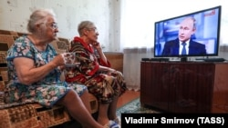 Elderly women watch a live broadcast of Russian President Vladimir Putin's annual question-and-answer session in the village of Yelna, Ivanovo region, on June 7.