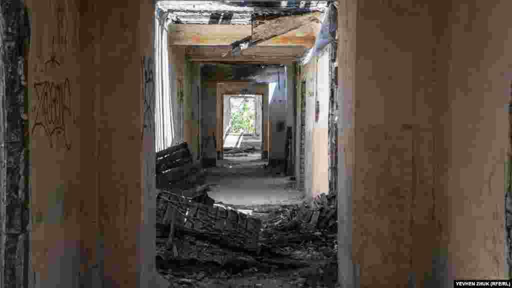 В коридор падает солнечный свет через дыры в крыше