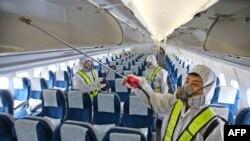 Южнокорейские рабочие дезинфицируют салон пассажирского самолета в международном аэропорту Incheon в Сеуле, 5 июня 2015 года.
