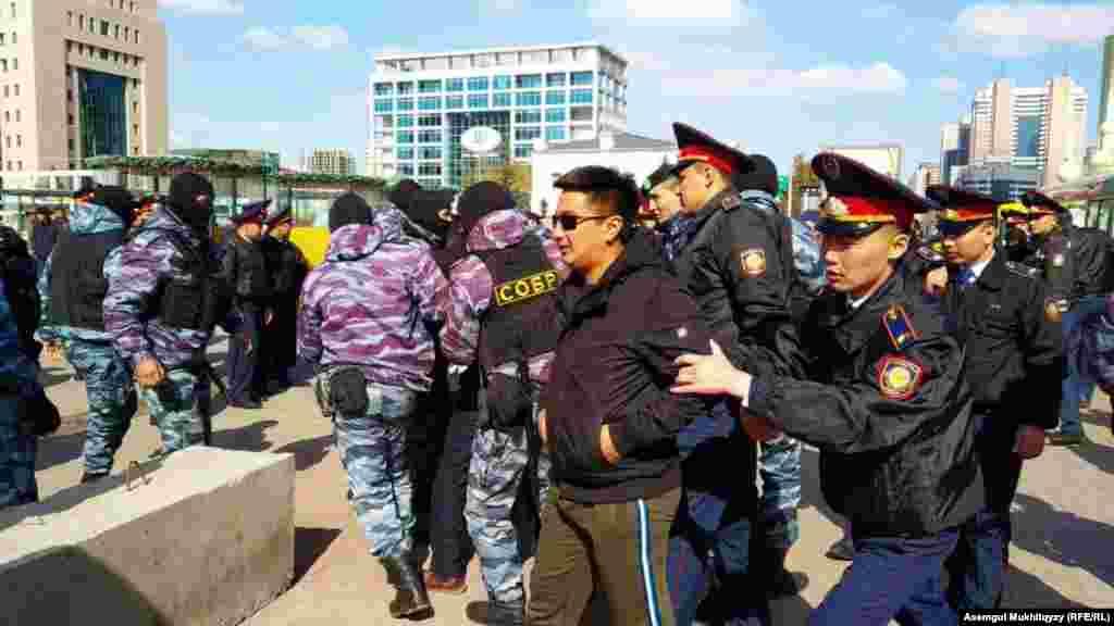 Полицейские задерживают людей в Нур-Султане, 1 мая 2019 года.
