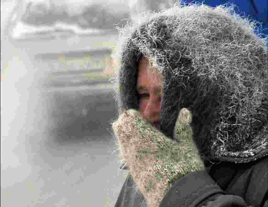 An elderly woman shields her face against the abnormally cold temperatures in the northeastern Kazakh city of Pavlodar, where temperatures reached minus 37 degrees Celsius. (AFP/Vladimir Bugayev)