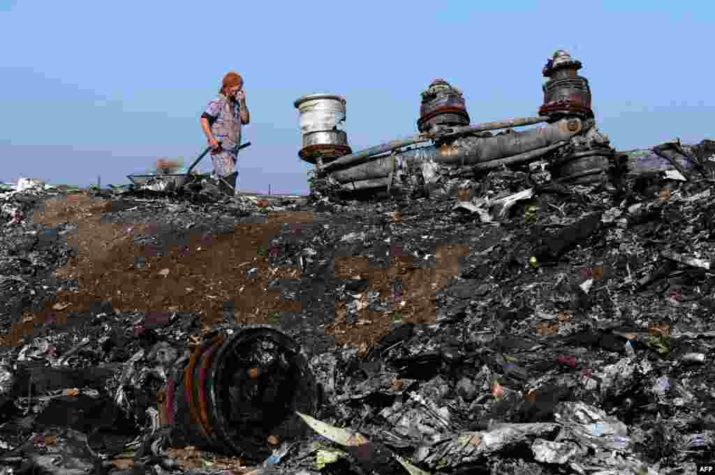 An elderly woman walks among the wreckage of Malaysia Airlines Flight MH17 that still lies near the village of Rassipnoye. (AFP/Dominique Faget)