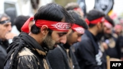 Iranian men cry during the Ashura commemorations that mark the killing of Imam Hussein, one of Shi'ite Islam's most revered figures, in Tehran on November 4.