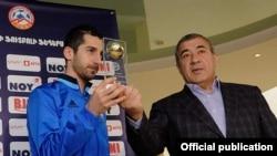 Armenia - Ruben Hayrapetian, chairman of the Football Federation of Armenia, hands an awards to Henrikh Mkhitaryan, the national football team captain, March 22, 2018.
