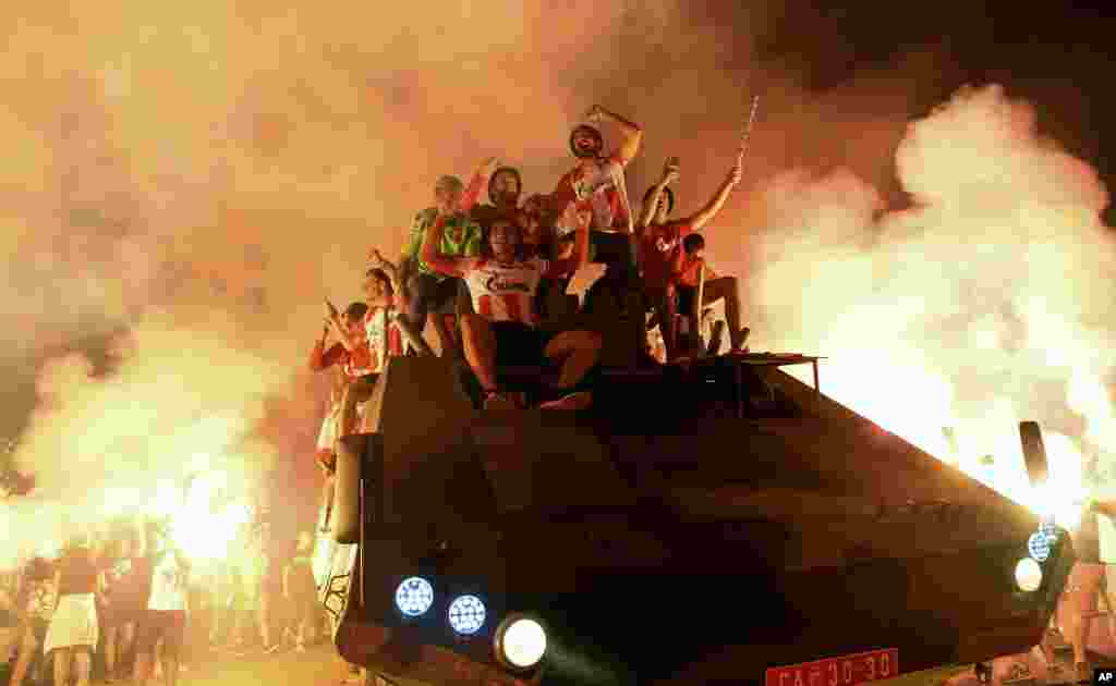 Supporters and players of the Red Star Belgrade soccer team celebrate qualifying for the Champions League with flares on top of an armored troop carrier in Belgrade on August 27.  (AP)