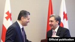 Georgia - Prime Minister Nika Gilauri (R) and his Armenian counterpart Tigran Sarkisian exchange copies of a memorandum signed after talks in Batumi, 19Nov2011.