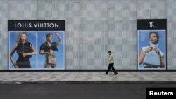 Një person kalon pranë një dyqani të mbyllur të firmës franceze Louis Vuitton . Fotografi nga arkivi.