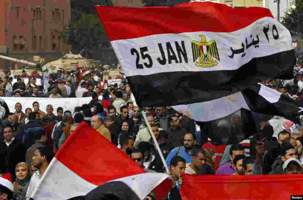 An Egyptian flag with January 25 -- the date the uprising started -- written on it is seen amid the crowd near army tanks on Tahrir Square on February 11, 2011.
