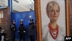A supporter of Yulia Tymoshenko holds her portrait during rally in front of a prison in Kyiv last year.