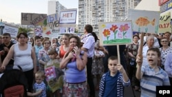 Residents of Moscow's Ramenki district hold posters with slogans such as 'No to killer road' as they protest against the decision of city authorities on a road separating residential areas and schools.