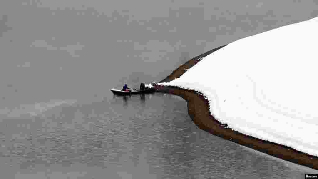 Two men fish on a lake after a snowfall near the Albanian city of Kukes, some 160 kilometers north of the capital, Tirana. (Reuters/Arben Celi)