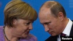 Германия канцлері Ангела Меркель (сол жақта) мен Ресей президенті Владимир Путин баспасөз мәслихатында сөйлесіп отыр. Санкт-Петербург, 21 маусым 2013 жыл.