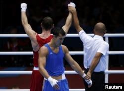 Казахстанский боксер Адильбек Ниязымбетов (в синем), ставший серебряным призером на Олимпиаде. Лондон, 12 августа 2012 года.