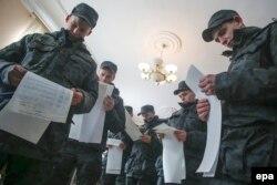 Membri ai Gărzii Naționale inspectînd un centru de vot