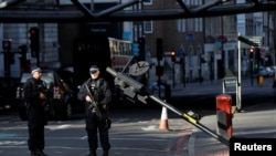Armed police officers stand near the site where attackers crashed their van after running over pedestrians on London Bridge, next to Borough Market, in central London on June 3