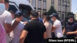 Сотрудники в штатском заталкивают задержанных в микроавтобус. Шымкент, 1 июля 2021 года