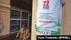 A shopper in Tashkent walks past a campaign poster for Uzbekistan's upcoming parliamentary elections on December 22.