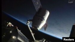 The SpaceX Dragon craft is seen during its maiden voyage to the International Space Station (attached) as it was prepared for its return to Earth in June 2012.