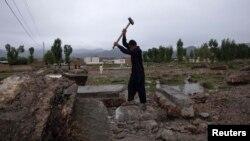 Мальчик-подросток откалывает кувалдой куски бетона фундамента виллы, где укрывался Усама бен Ладен. Абботтабад, 22 апреля 2012 года.