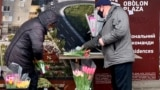 A customer buys a bouquet of tulips near a subway station in Kyiv. Somewhere along the line, calls for women's rights and equality were eclipsed by gifts of greeting cards, bouquets, and sweets.