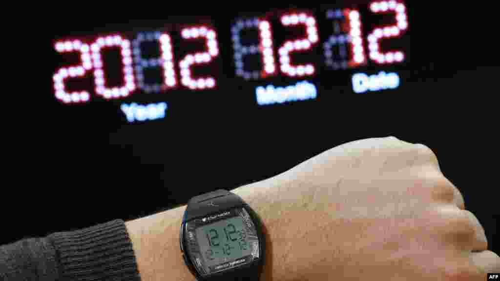 "A watch on a person's wrist reading the time ""12:12"" and the date ""12-12-12"" for December 12, 2012, in front of a digital clock reading ""December 12, 2012"" in Paris. It's the 21st century's last sequential date. (AFP/Thomas Coex)"