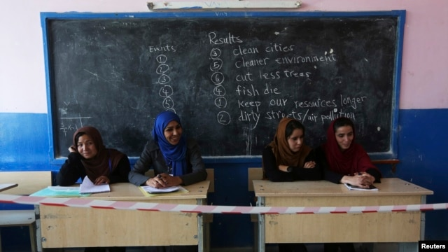 Afghan observers sit at a polling station in Kabul in the second round of the presidential election on June 14.
