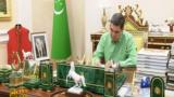 Президент Туркменистана за рабочим столом, уставленным фотографии и статуэтками собак и лошадей. Кадр из репортажа гостелевидения Туркменистана. Государственные СМИ пропагандируют имидж президента - ценителя и знатока собак породы алабай и лошадей ахалтекинской породы.