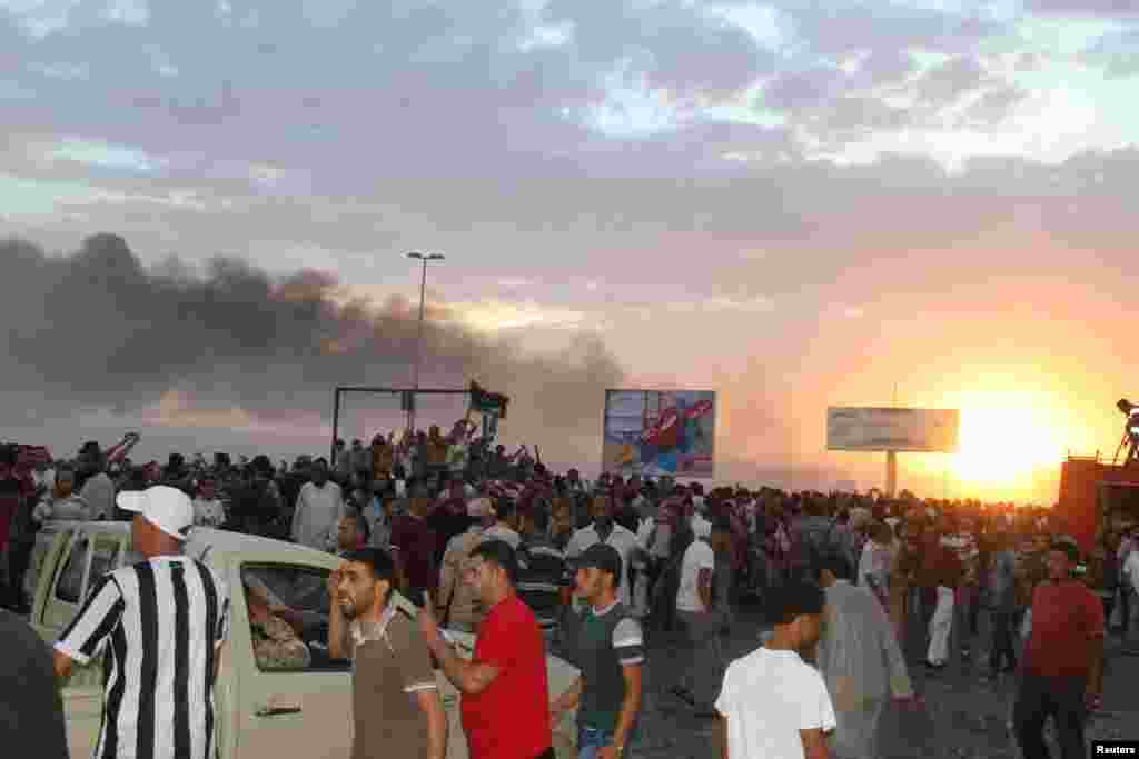 People gather at the scene of a Libyan warplane crash in the eastern city of Tobruk. (Reuters/Stringer)