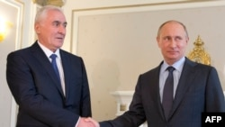 Russian President Vladimir Putin (right) shakes hands with the leader of Georgia's breakaway province of South Ossetia, Leonid Tibilov, during their meeting in Russia's Black Sea resort of Sochi in May 2013.