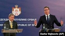 Serbian President Aleksandar Vucic (right) speaks at a press conference after talks with EU Enlargement Commissioner Johannes Hahn (left) in Belgrade on February 7.