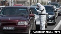 Yerevanda polis əməkdaşı avtomobili yoxlayır, 12 aprel, 2020-ci il